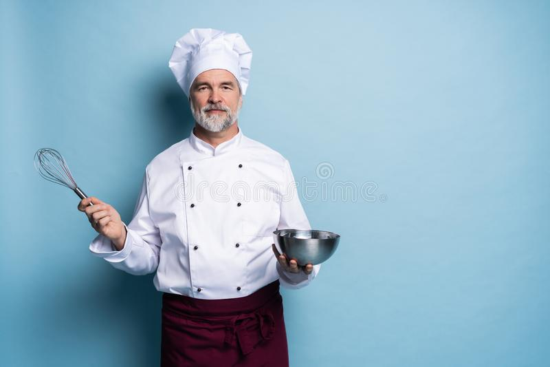 Portret u?miechni?ty szefa kuchni mienia drutu i pucharu ?migni?cie na b??kitnym tle Szef kuchni robi posi?kowi obrazy stock