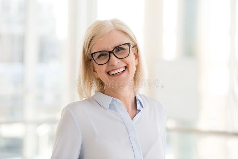 Portret uśmiechnięty w średnim wieku bizneswoman pozuje dla obrazka fotografia stock
