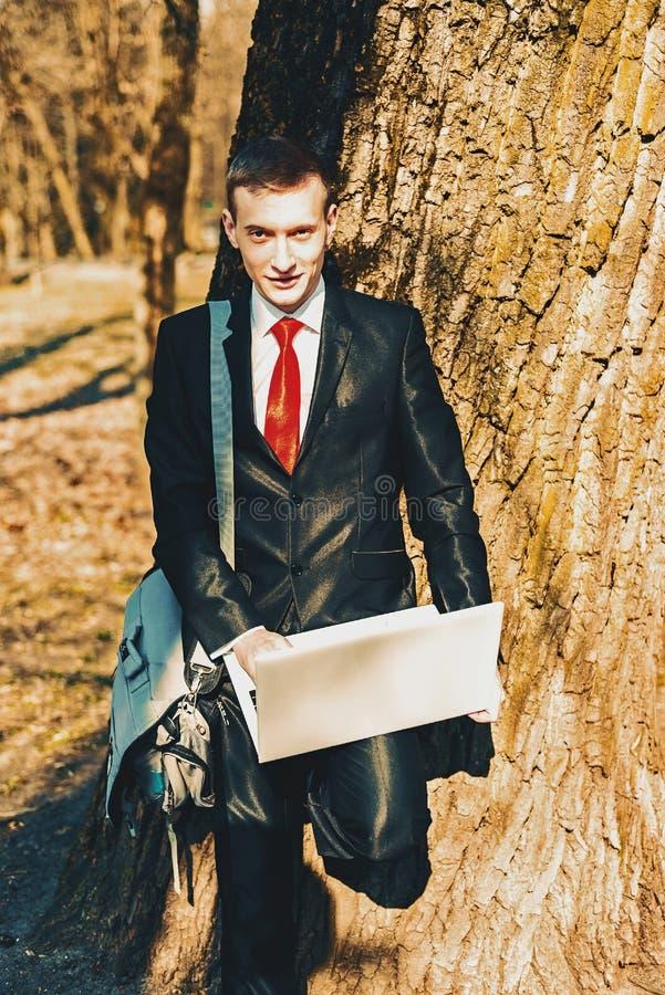 Portret uczeń w czarnym kostiumu czerwonym krawacie na naturze blisko wielkiego drzewa i na ramieniu młoda facet torba freelancer obraz royalty free