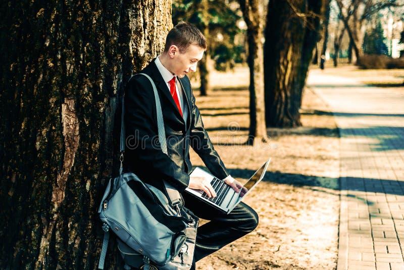 Portret uczeń w czarnym kostiumu czerwonym krawacie na naturze blisko wielkiego drzewa i na ramieniu młoda facet torba freelancer zdjęcie royalty free