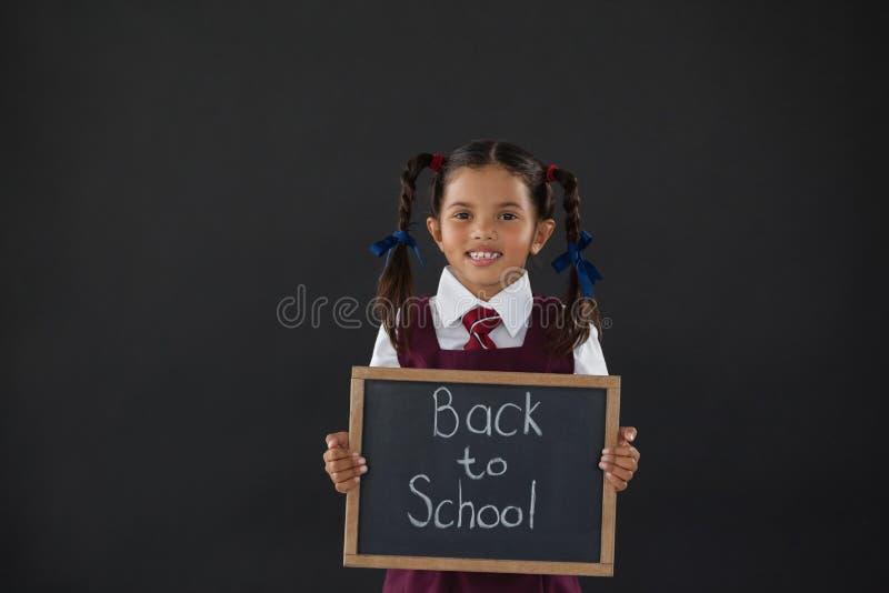 Portret uczennicy mienia łupek z tekstem przeciw blackboard fotografia royalty free
