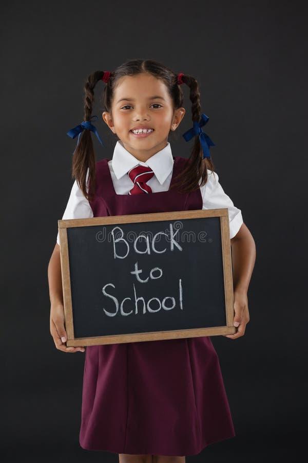 Portret uczennicy mienia łupek z tekstem przeciw blackboard obraz stock