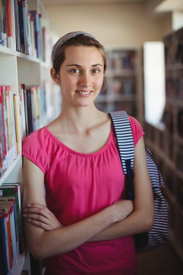 Portret uczennicy pozycja z rękami krzyżował w bibliotece fotografia stock