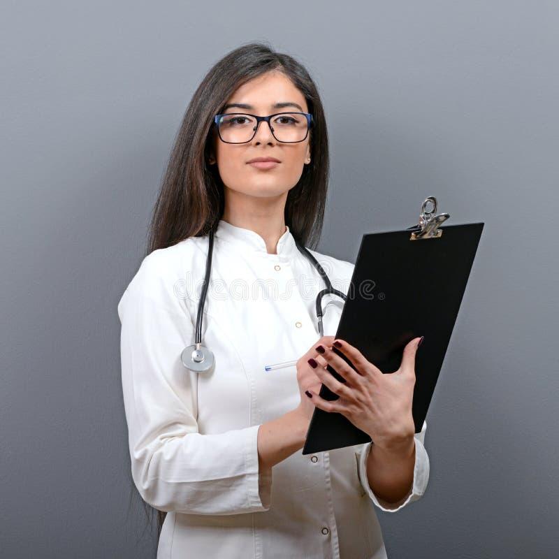 Portret ufna lekarz medycyny kobieta pisze na schowku przeciw szaremu tłu zdjęcia stock