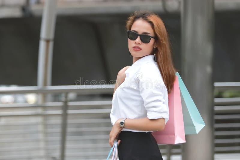 Portret ufna młoda Azjatycka kobieta niesie kolorowego torba na zakupy na ramieniu obrazy royalty free