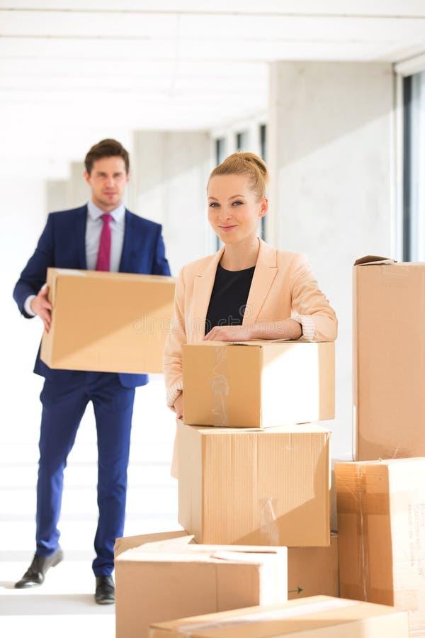 Portret ufna młoda bizneswoman pozycja brogującymi pudełkami z męskim kolegą w tle przy biurem zdjęcia royalty free
