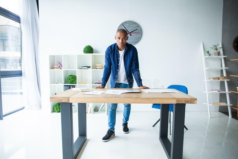 Portret ufna młody człowiek pozycja przy jego biurkiem z laptopem Afrykański biznesmen pracuje w nowożytnym biurze obraz stock