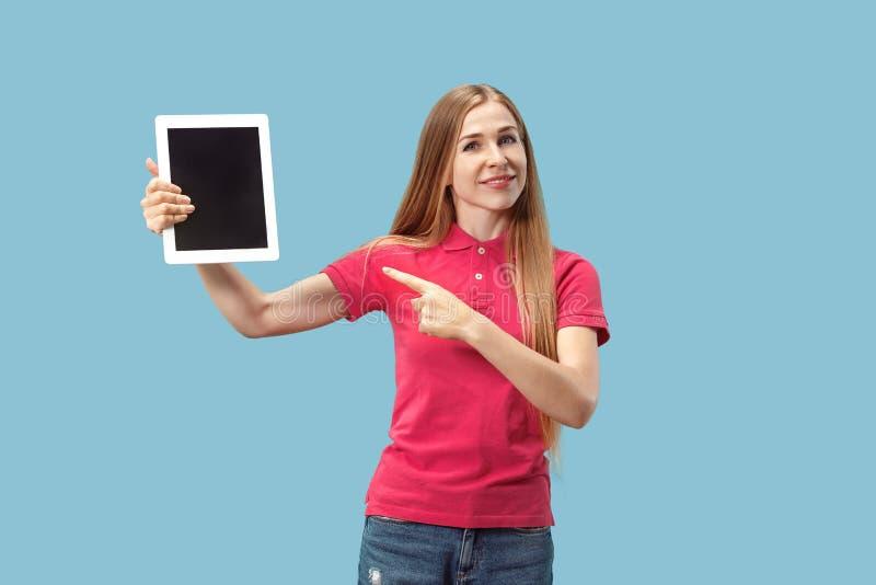 Portret ufna przypadkowa dziewczyna pokazuje pustego ekran odizolowywającego nad błękitnym tłem laptop obraz stock