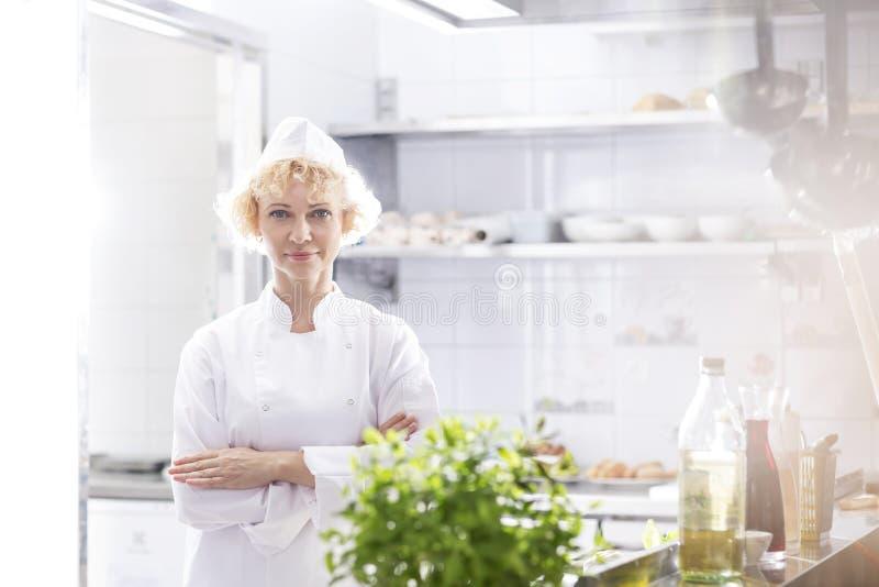 Portret ufna szef kuchni pozycja z rękami krzyżował w kuchni przy restauracją zdjęcie stock