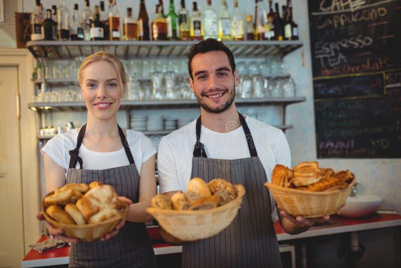 Portret ufni pracownicy z świeżym chlebem w koszach zdjęcia stock