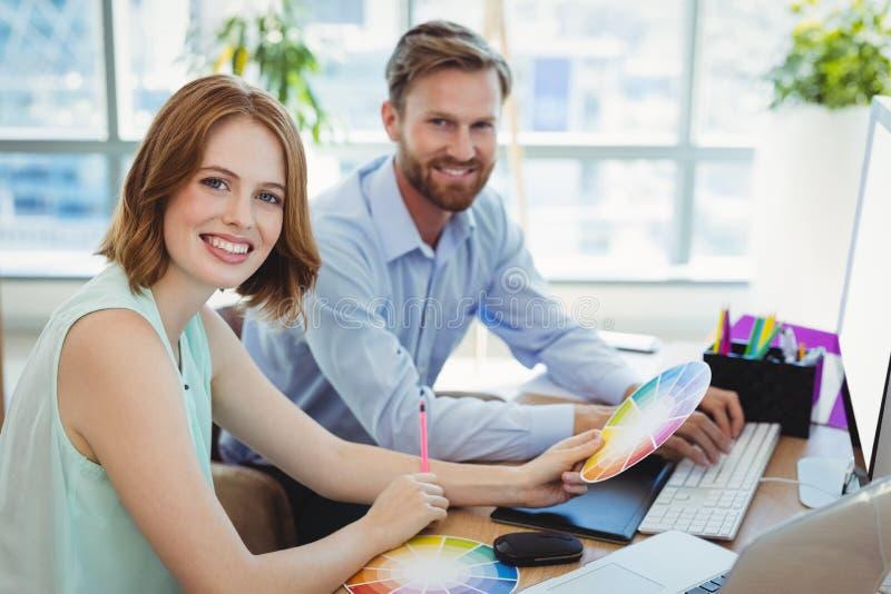 Portret ufni projektant grafik komputerowych pracuje przy biurkiem zdjęcie royalty free