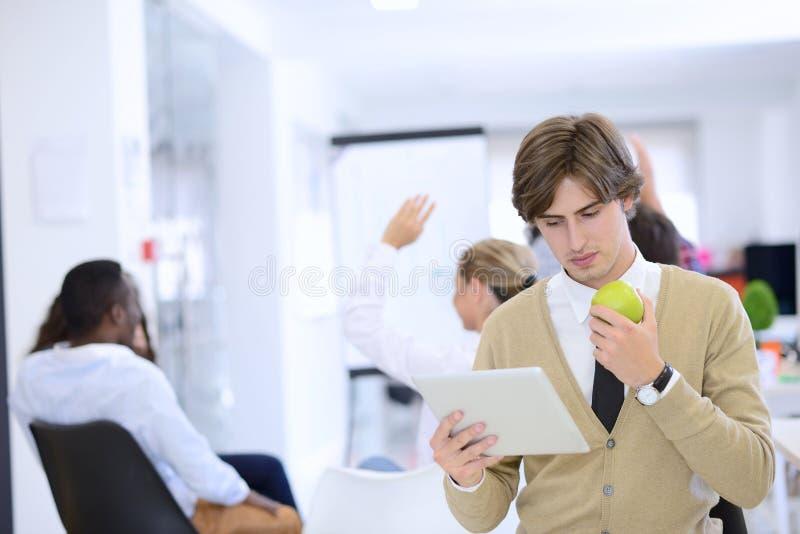 Portret ufny biznesmen używa cyfrową pastylkę w tle podczas gdy kolega zdjęcie stock
