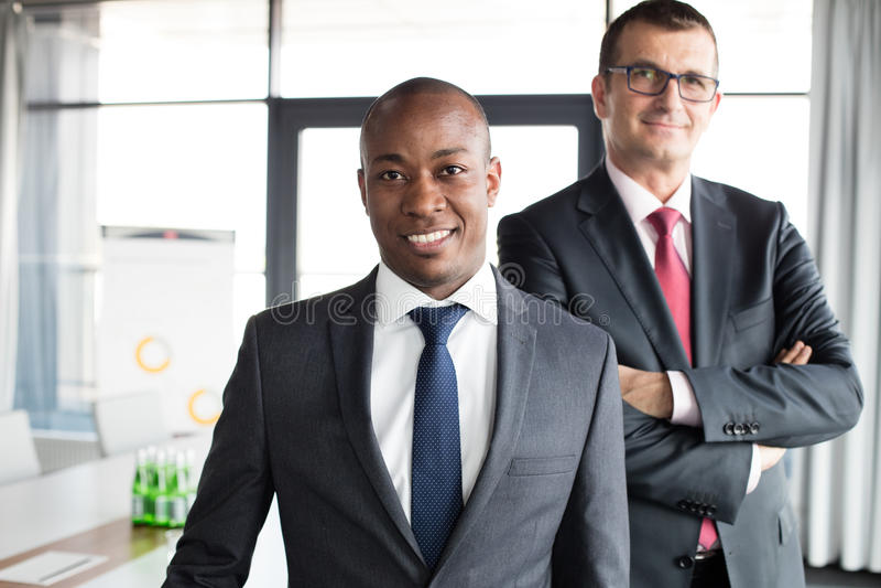 Portret ufny biznesmen z męskim kolegą w biurze obraz stock