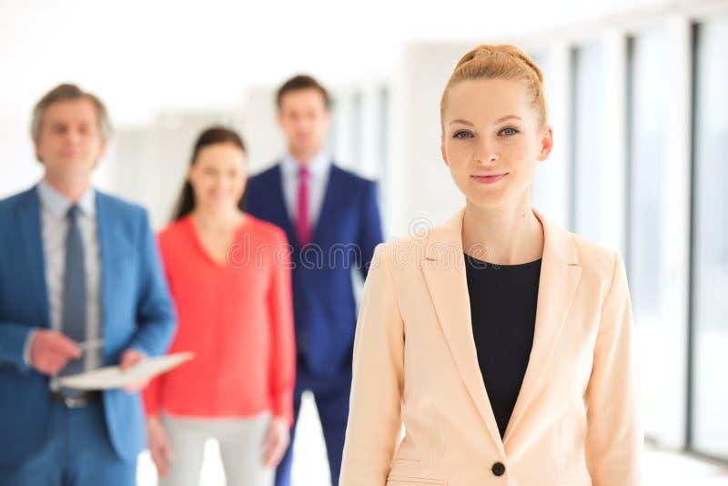 Portret ufny bizneswoman z kolegami w tle przy biurem fotografia royalty free