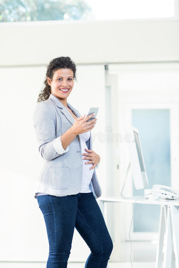Portret ufny ciężarny bizneswoman używa telefon zdjęcia royalty free