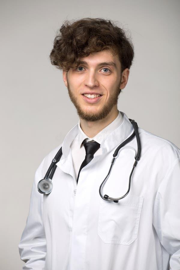 Portret ufny młody uśmiechnięty lekarz medycyny z sthetoscope zdjęcia stock