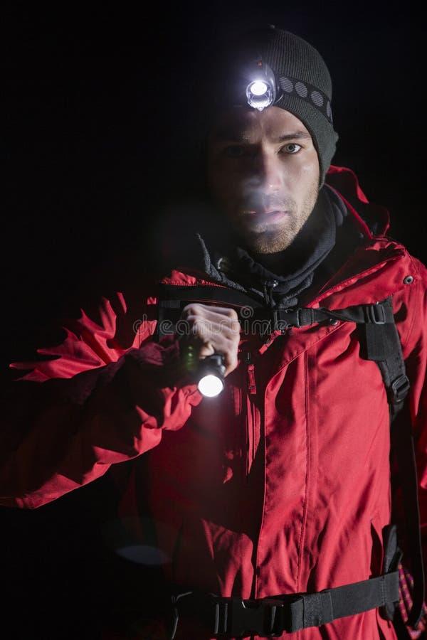 Portret ufny męski wycieczkowicz z latarką przy nocą zdjęcia royalty free