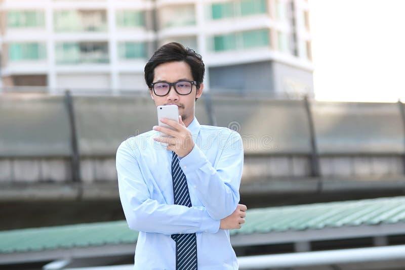 Portret ufny młody Azjatycki biznesowego mężczyzna przyglądający mobilny mądrze telefon przy outside biurem obraz stock