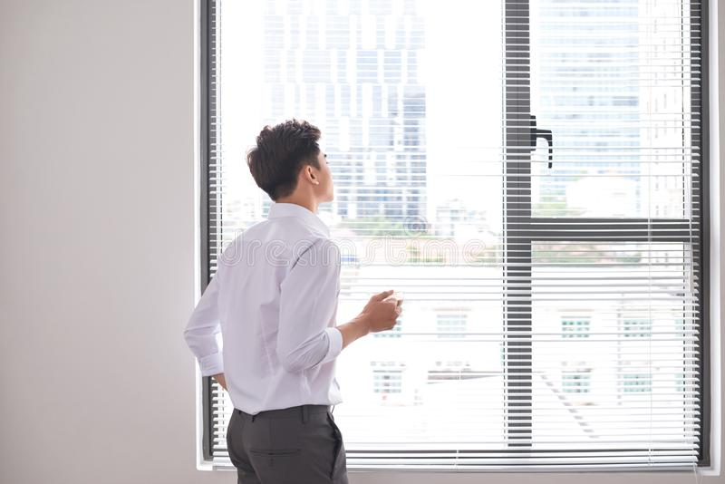 Portret ufny młody biznesmen trzyma filiżanka kawy podczas gdy stojący blisko biurowych nadokiennych, inteligentnych mężczyzn w b zdjęcia stock