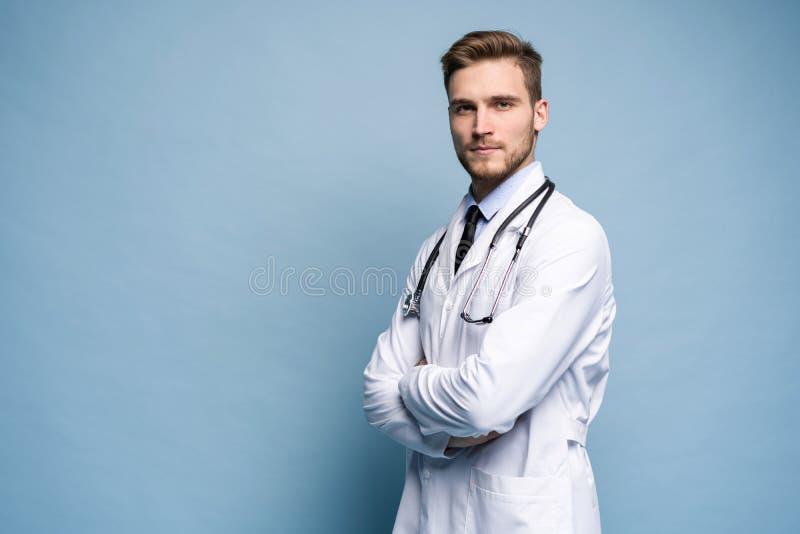 Portret ufny młody lekarz medycyny na błękitnym tle fotografia stock