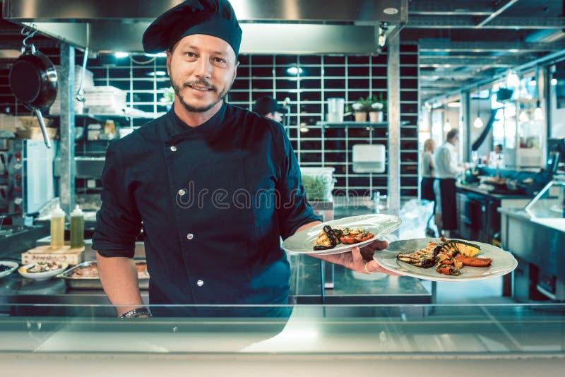 Portret ufny mistrzowski szef kuchni trzyma dwa talerza z smakowitym jedzeniem fotografia royalty free