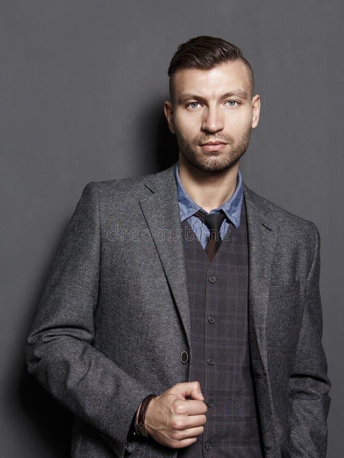 Portret ufny przystojny biznesmen w kostiumu na szarość izoluje tło Modni piękni mężczyzna spojrzenia przy ramą obraz stock
