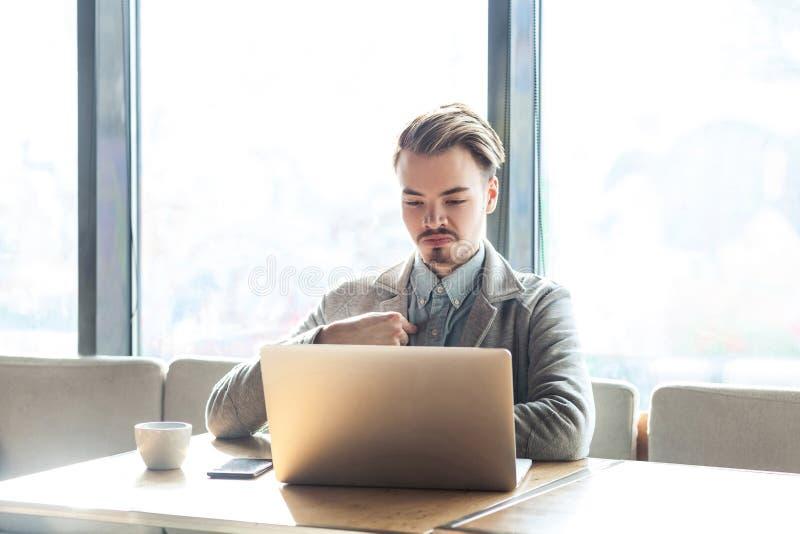 Portret ufny samolubny zadowolony egoistyczny brodaty młody freelancer w popielatym blezerze siedzi w kawiarni, pracuje na laptop zdjęcia stock