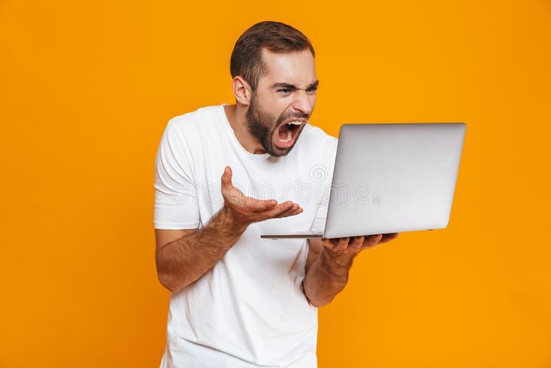 Portret uptight mężczyzna 30s w białej koszulce krzyczy srebnego laptop i trzyma, odizolowywający nad żółtym tłem zdjęcie royalty free