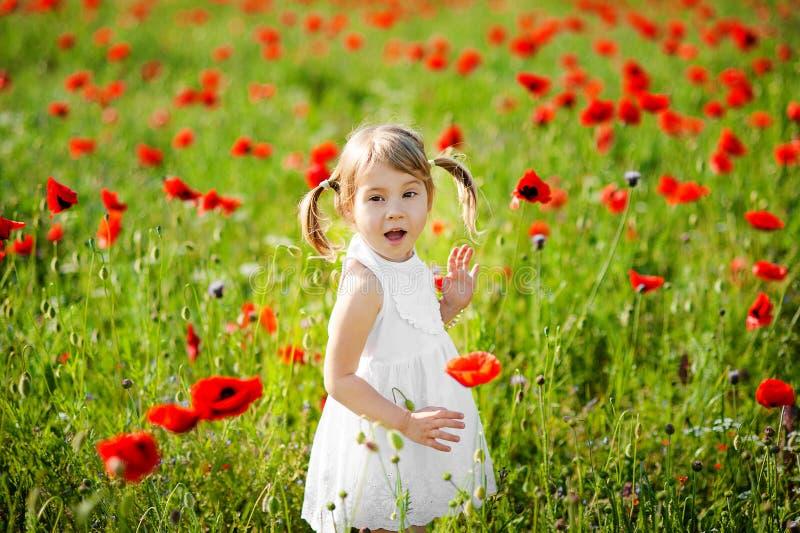 Portret urocza berbeć dziewczyna zaskakuje w białej smokingowej sztuce w pięknym polu czerwoni maczki zdjęcie stock