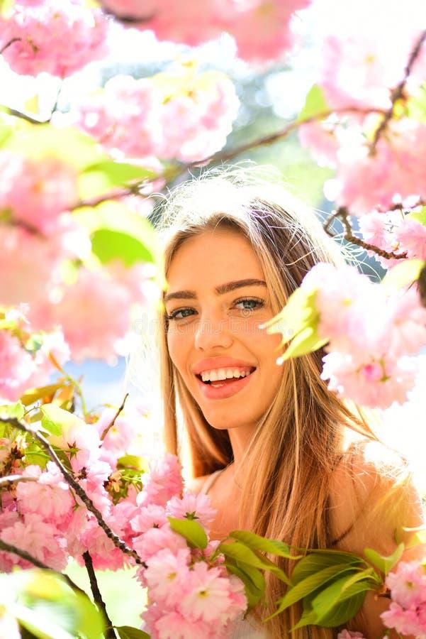 Portret urocza blond dziewczyna otaczająca różowymi płatkami Kobieta z dużymi oczami i powabnym uśmiechem na naturalnym tle zdjęcia stock