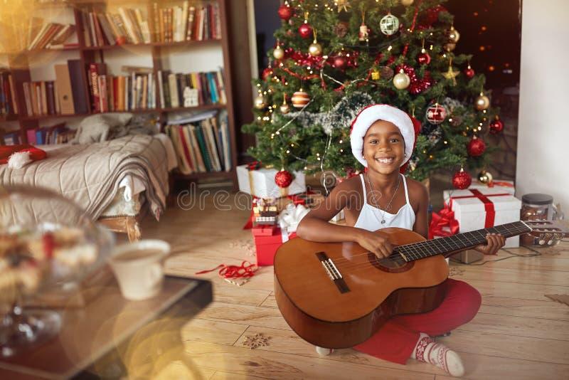 Portret urocza dzieciak dziewczyna bawić się gitarę - ludzie, boże narodzenia zdjęcie royalty free