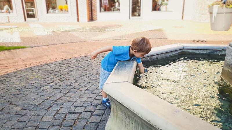 Portret urocza 3 lat berbecia ch?opiec macania woda w fontannie przy parkiem zdjęcia royalty free