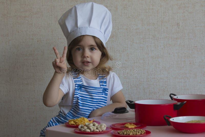 Portret Urocza mała dziewczynka w szefa kuchni kapeluszu kucharza jedzeniu przedstawienia dotykają zwycięstwo zdjęcie royalty free