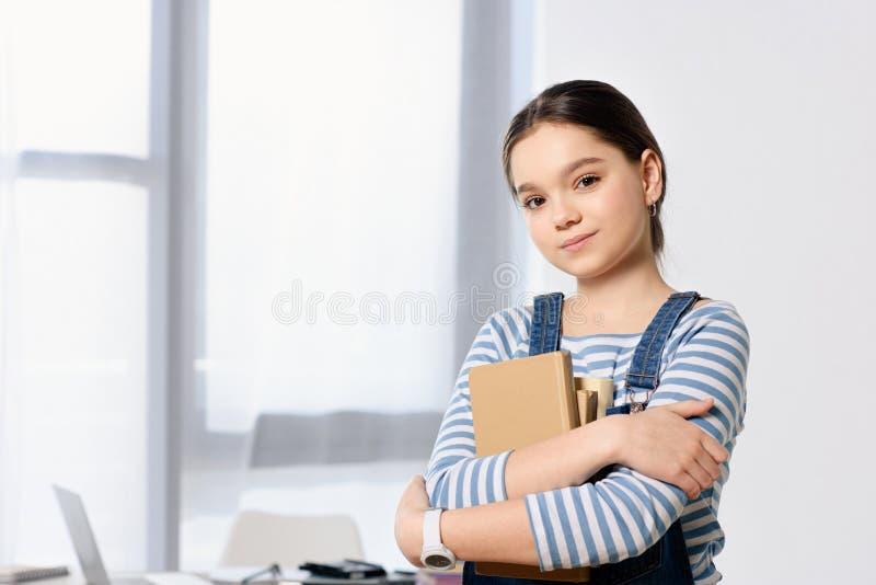 portret urocza preteen dziecko pozycja z książkami zdjęcia royalty free