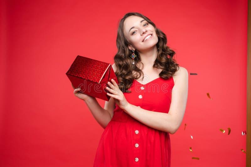 Portret urocza uśmiechnięta młoda kobieta z długim kędzierzawym włosy pozuje przy czerwonym pracownianym tłem fotografia stock