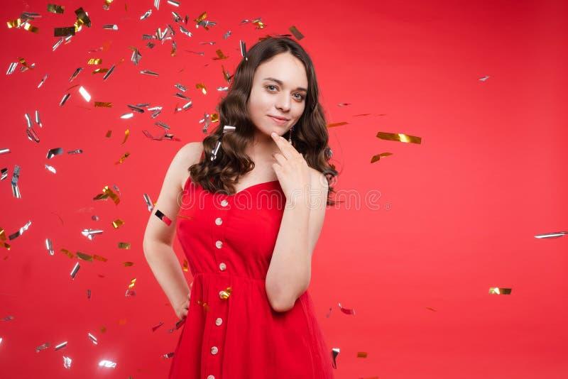 Portret urocza uśmiechnięta młoda kobieta z długim kędzierzawym włosy pozuje przy czerwonym pracownianym tłem zdjęcia stock