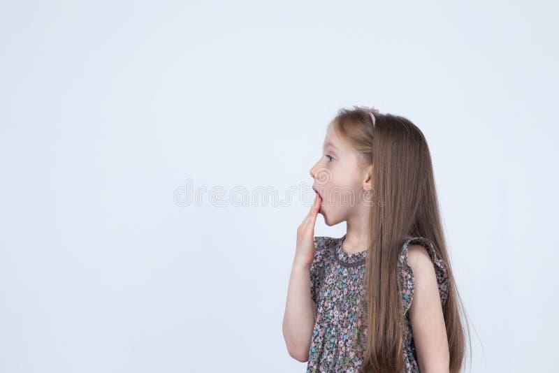 Portret urocza zdziwiona zdumiewająca mała dziewczynka odizolowywająca na bielu Dziewczyny dziecka mienia ręki przy usta zaskakuj obraz royalty free