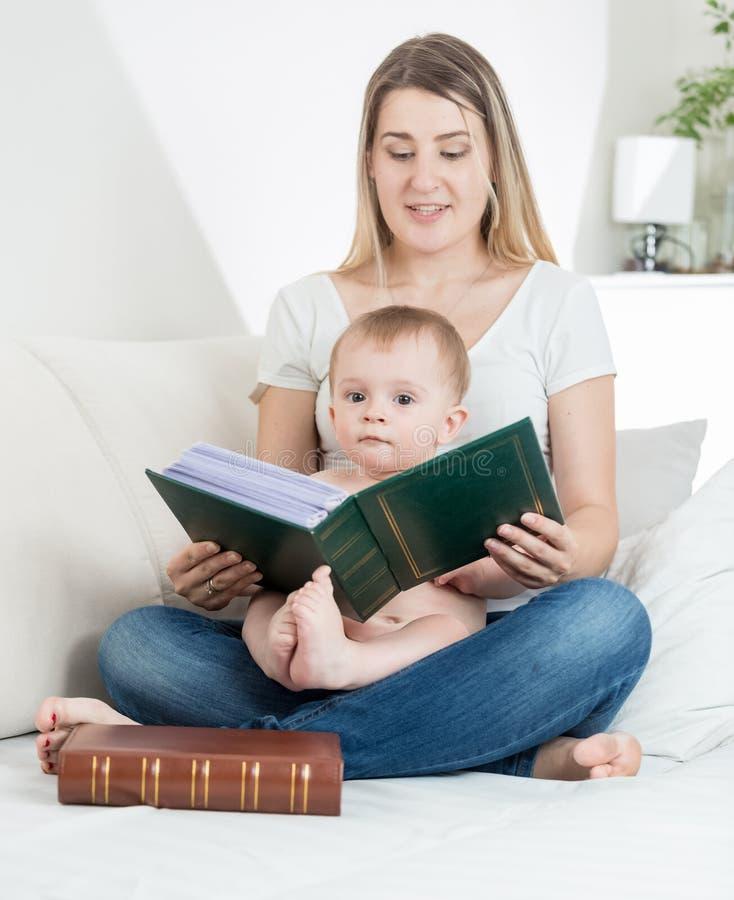 Portret uroczy chłopiec obsiadanie z potomstwo matką na łóżka i czytania dużej starej książce fotografia royalty free