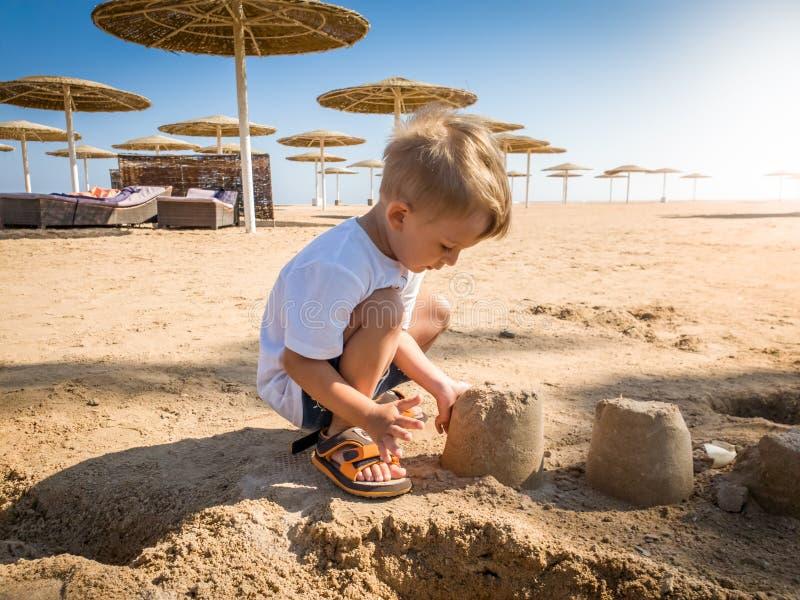 Portret uroczy 3 lat berbecia chłopiec obsiadanie na piaskowatej morze plaży i budynek roszujemy Dziecko relaksuje dalej zdjęcia stock