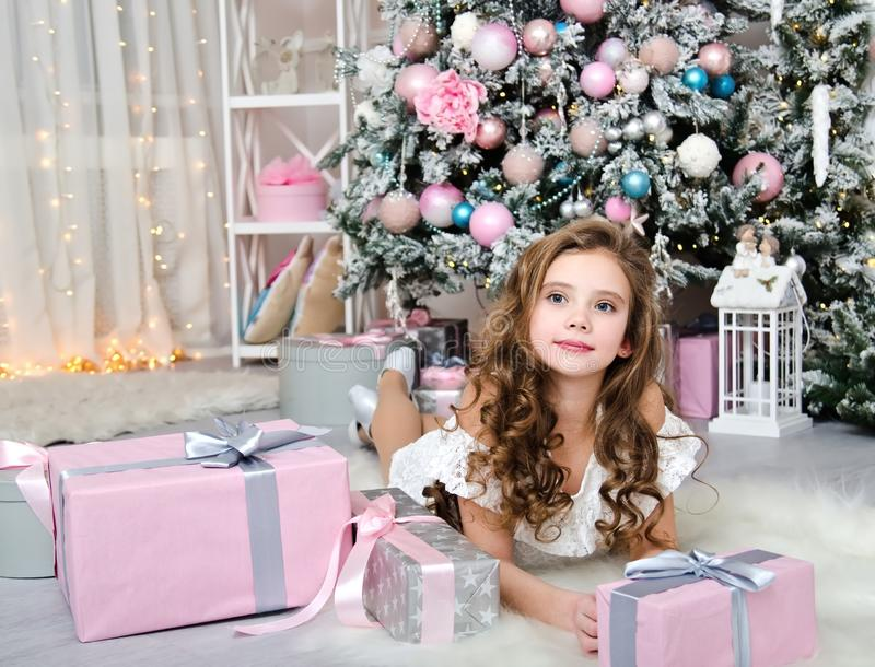 Portret uroczy szczęśliwy uśmiechnięty małej dziewczynki dziecko kłama blisko jedlinowego drzewa w princess sukni z prezentów pud obraz royalty free