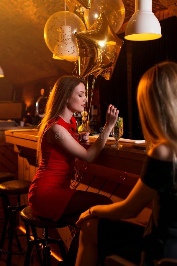 Portret urodzinowy dziewczyny obsiadanie z szkłem koktajl przy baru kontuarem obraz stock