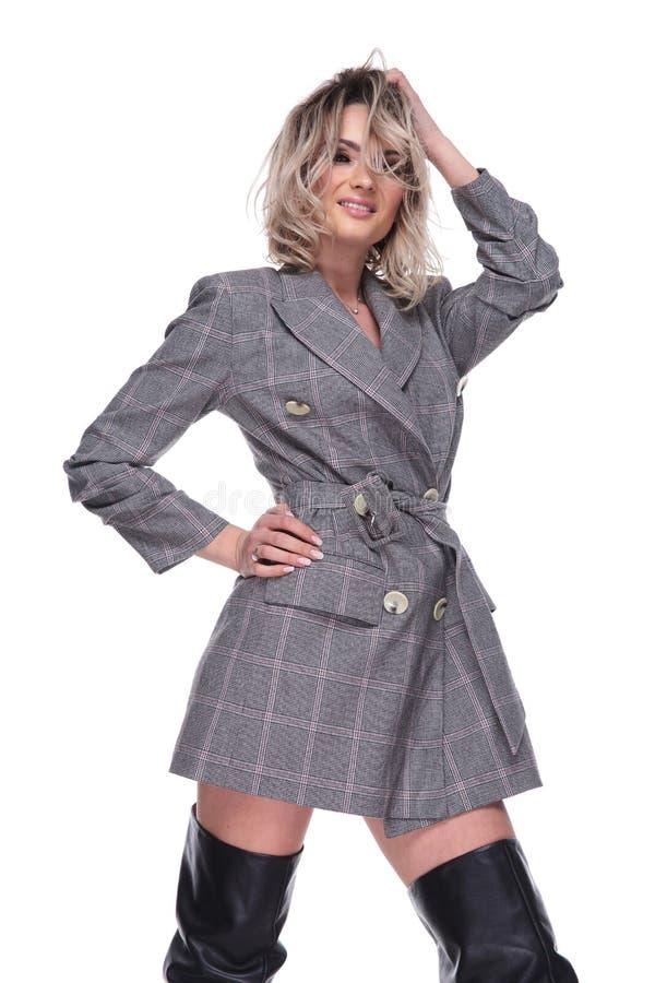 Portret uwodzicielska kobieta w popielatej kurtce układa jej włosy obrazy royalty free