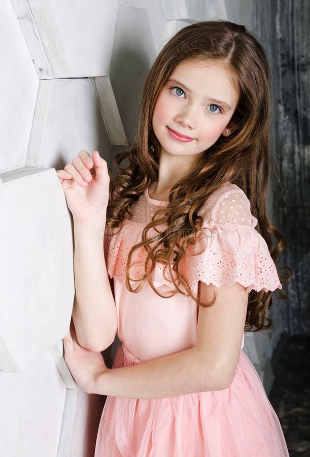 Portret van aanbiddelijk glimlachend bevindend meisjekind stock foto's