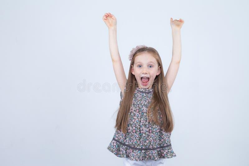 Portret van aanbiddelijk glimlachend die meisje op een wit wordt geïsoleerd Peuter met haar omhoog handen Gelukkig Kind Vrolijke  royalty-vrije stock afbeelding