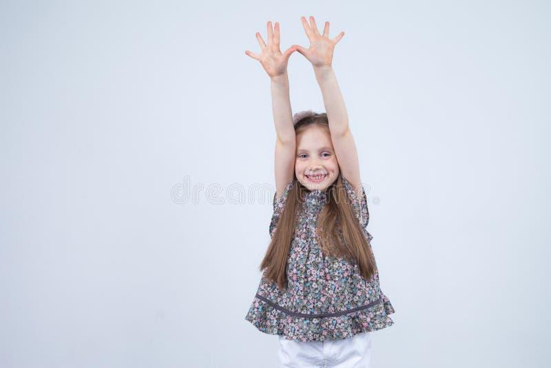 Portret van aanbiddelijk glimlachend die meisje op een wit wordt geïsoleerd Peuter met haar omhoog handen Gelukkig Kind Vrolijke  royalty-vrije stock fotografie