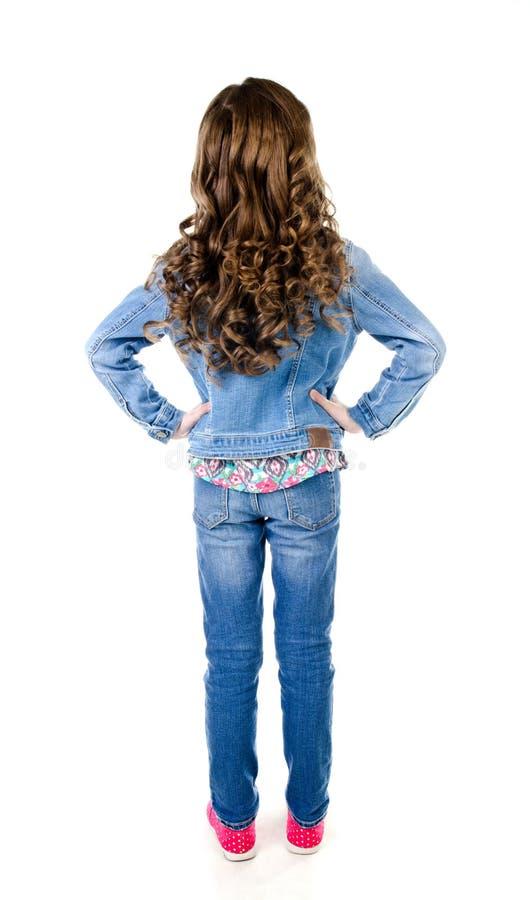 Portret van aanbiddelijk meisje in jeans die achteruitgaan stock afbeelding