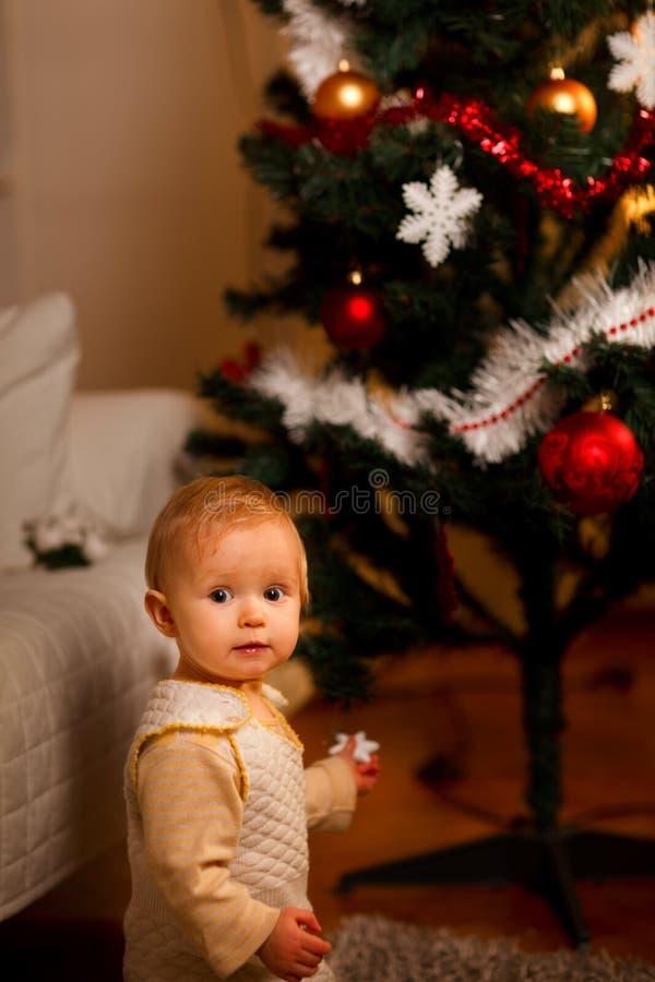 Portret van aanbiddelijke baby dichtbij Kerstboom royalty-vrije stock foto's