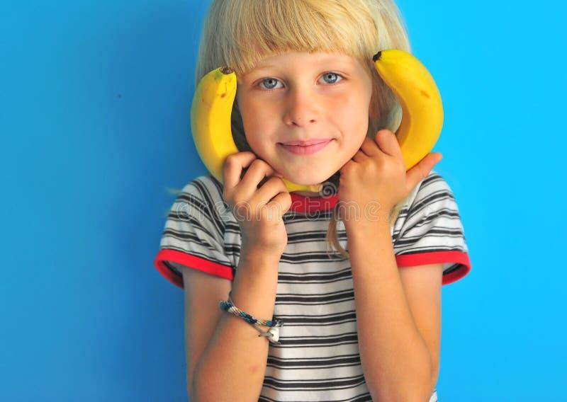 Portret van aanbiddelijke blondejongen met bananen royalty-vrije stock foto's