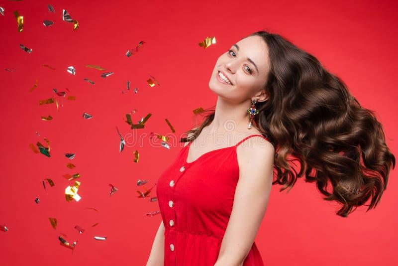 Portret van aanbiddelijke glimlachende jonge vrouw met het lange krullende haar stellen bij rode studioachtergrond stock foto