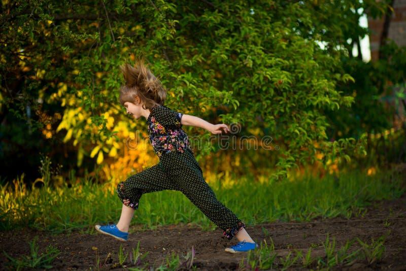 Portret van aanbiddelijke het glimlachen meisjessprong in park bij zonsondergang royalty-vrije stock foto's